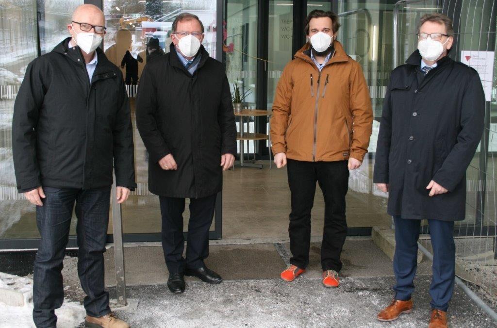 Vier Männer stehen vor einer Eingangstür.